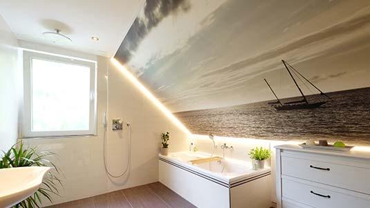 Badezimmerdecke in Weiß mit kreativ gestalteter Fotodecke an der Dachschrägen. Die umlaufende LED-Beleuchtung sorgt für gemütliches Licht beim Baden.
