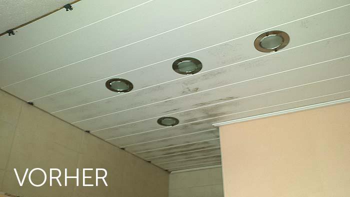 Vor der Deckenrenovierung. Die alte Holzpaneele an der Decke schimmelt im Bereich der Dusche.
